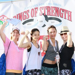 Rings of Strength participants pose with a backdrop