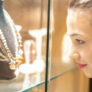 woman peering through glass at necklaces