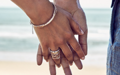 A man and womans hands on a beach