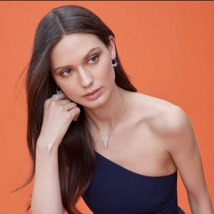 Model wearing jewelry against orange background