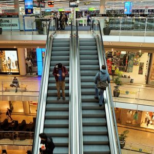 shopping center interior with customers on escalators