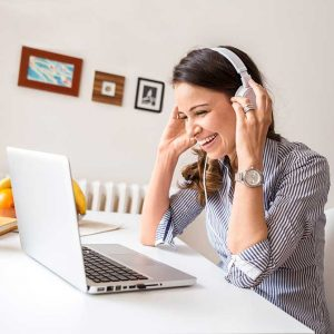 woman at laptop wearing headphones