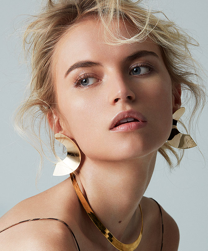 model in sculptural gold earrings