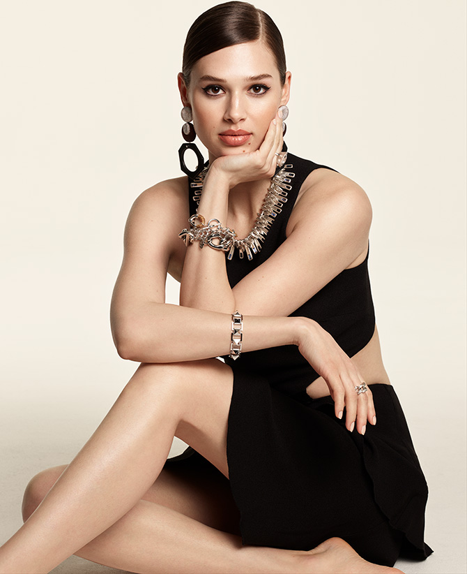 Model in black dress with metallic jewelry
