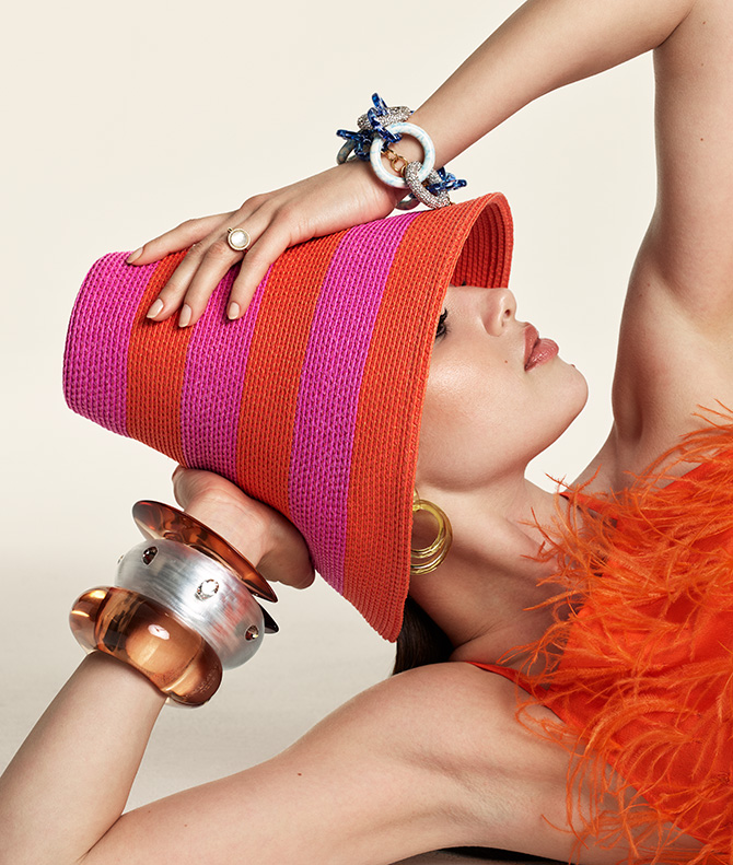 Model in pink hat and orange feathers with bracelets