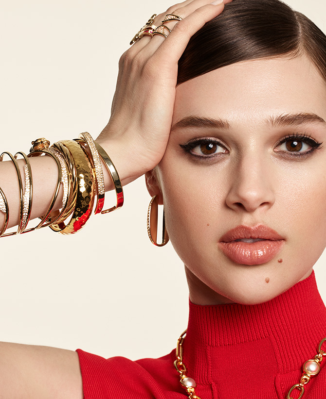 Model in red turtleneck with gold bracelets