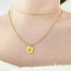 gold pendant necklace on neck