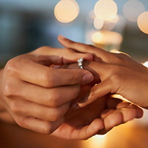 large hands placing engagement ring on smaller hand