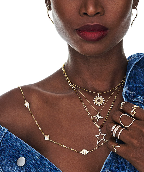 Model in denim with layered delicate necklaces