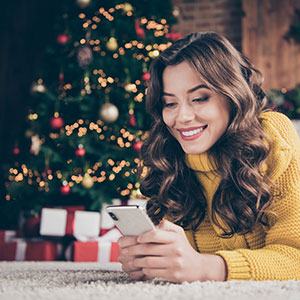 Girl with phone in front of christmas tree