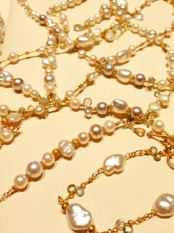 Necklaces and a bracelet in karat gold with white pearls and sapphires by Laura Gibson