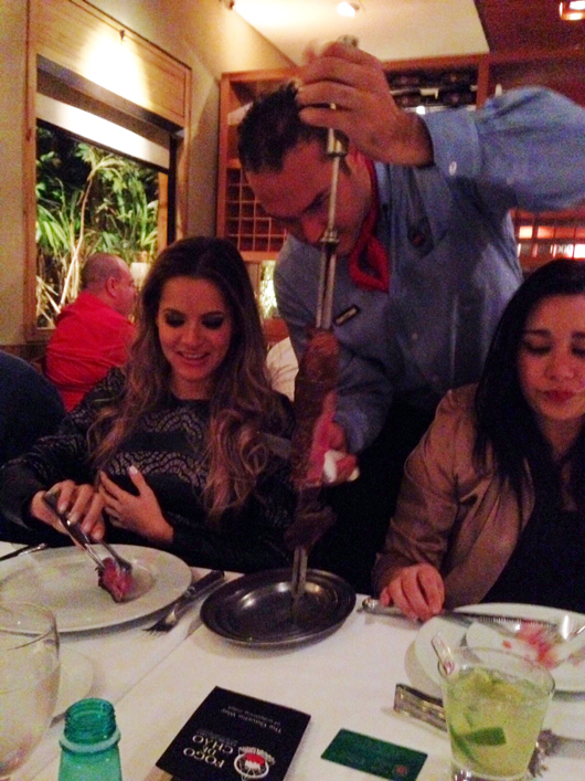 IBGM's Clarissa Maciel takes some steak from the roving meat man at Fogo de Chão last night.