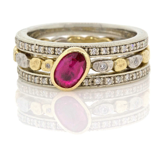 Trio of rings in Rona Fisher's Dancing Diamonds Pebbles jewelry collection in 18k gold and palladium and a ruby