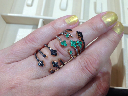 Stacking open rings in 18k gold with black and brown diamonds and emeralds by Vancox